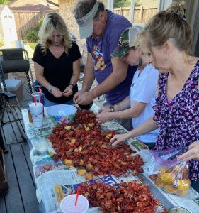 Line of people peeling crawfish.